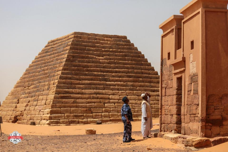 In this Thursday، April 16، 2015 photo، a Sudanese tour guide and a member of the security forces observes a temple at the Meroe pyramids site، in al-Bagrawiya، 200 kilometers (125 miles) north of Khartoum، Sudan. The pyramids at Meroe are deserted despite being a UNESCO World Heritage site like those at Giza in Egypt. (AP Photo/Mosa'ab Elshamy)