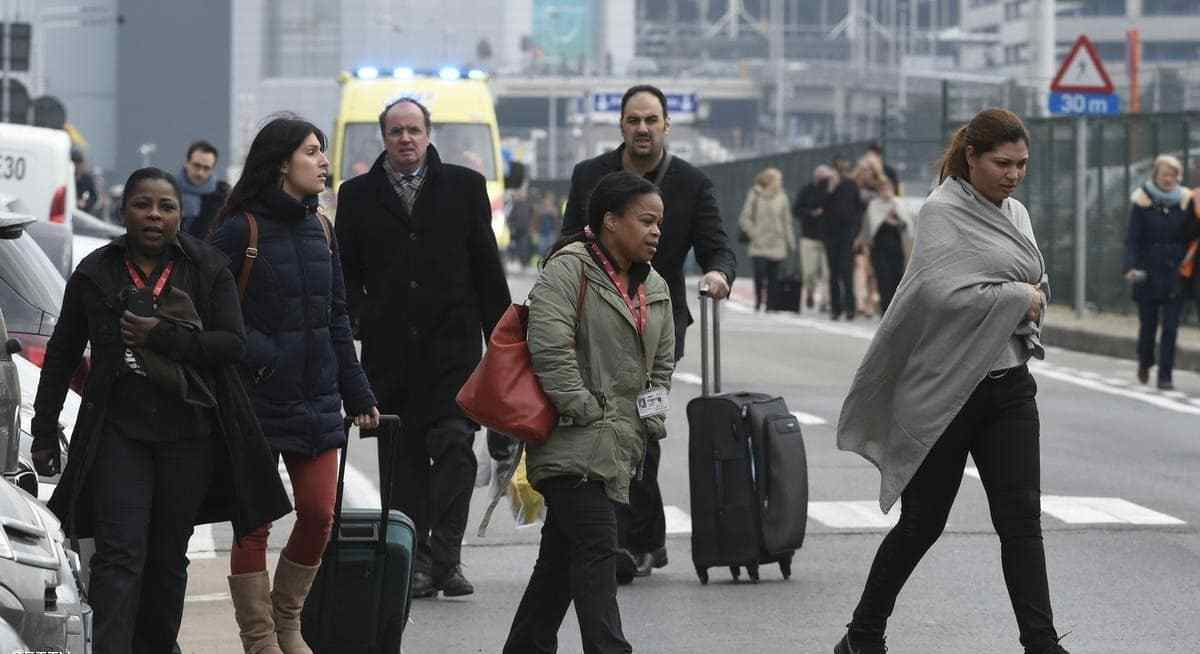 Passengers leave Brussels airport، on March 22، 2016 in Zaventem، following its evacuation after at least 13 people were killed and 35 injured as twin blasts rocked the main terminal of Brussels airport.AFP PHOTO / JOHN THYS / AFP / JOHN THYS (Photo credit should read JOHN THYS/AFP/Getty Images)