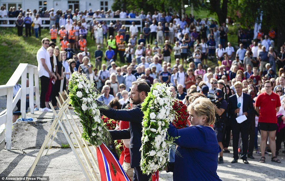 Crown Prince Haakon of Norway and Prime Minister Erna Solberg، right، lay wreaths during a ceremony on Utoya Island، Norway، Friday July 22، 2016. Norway is paying homage to the 77 people killed in a bombing and shooting rampage five years ago، with church services and events to mark one of the darkest days in the Scandinavian country's history. (Jon Olav Nesvold/NTB Scanpix via AP)